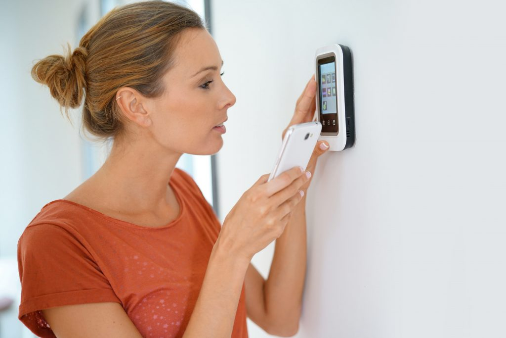 Woman using smartphone to control home connectivity